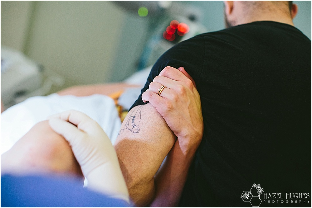 Woman grips man's arm during a contraction