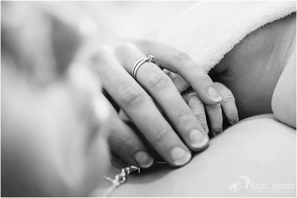 Mother holds newborn hand
